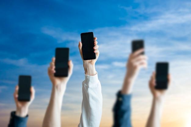 Un grand groupe de personnes détiennent un appareil de téléphonie numérique, de nombreuses mains humaines