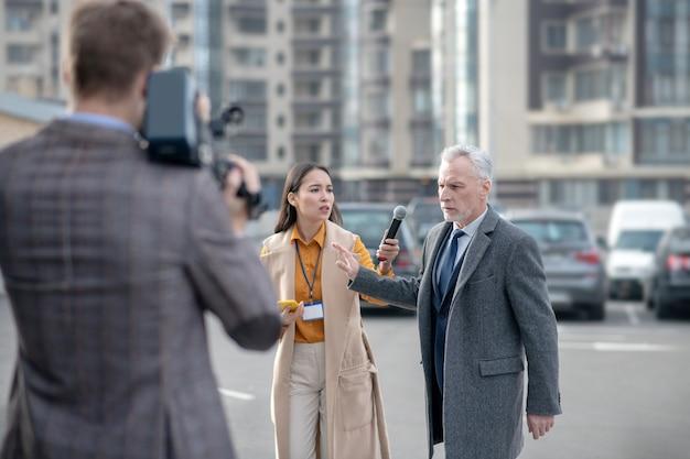 Grand homme avec caméra vidéo enregistrement vidéo avec célèbre homme d'affaires