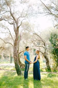 Grand homme dans un t-shirt bleu tient les mains de la femme enceinte dans une robe longue