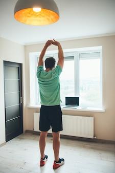 Grand homme de race blanche étirant son corps et pratiquer la remise en forme à domicile en regardant l'ordinateur portable