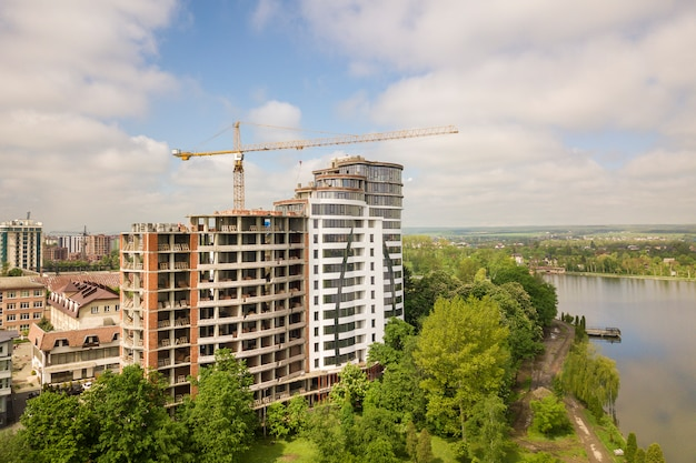 Grand immeuble ou immeuble de bureaux inachevé en cours de construction entre des cimes d'arbres verts. grues à tour sur un ciel bleu lumineux.