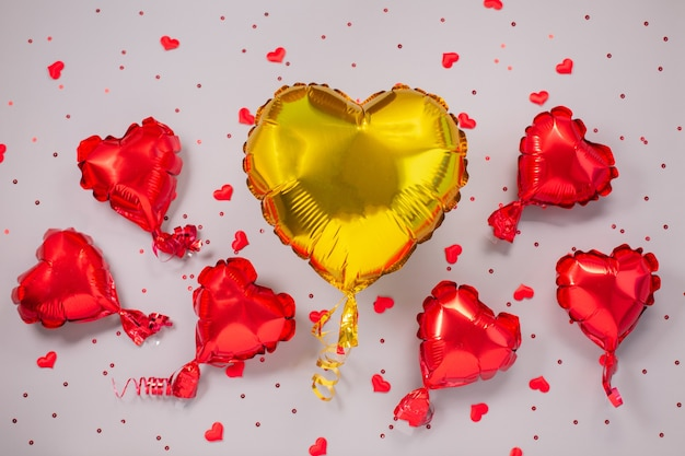 Un grand jaune et plusieurs petits ballons à air rouges en aluminium en forme de coeur. concept d'amour. la saint-valentin