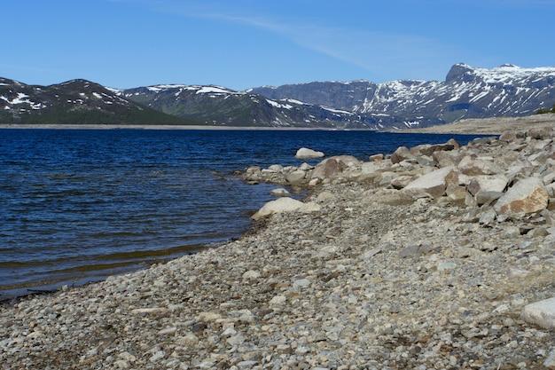 Grand lac de montagne avec des montagnes enneigées en arrière-plan, norvège