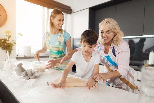 La grand-mère aide le garçon, la mère est à côté et regarde