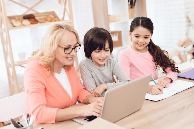 Une grand-mère aide ses petits-enfants à faire leurs devoirs