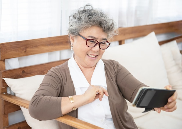Grand-mère aînée à l'aide de téléphone faire selfie à la maison