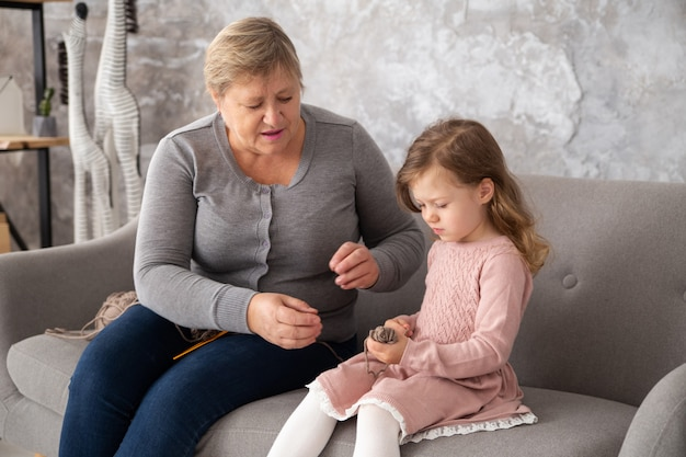 Grand-mère aînée tricotant avec sa petite-fille à la maison familiale. femme avec petite fille au crochet assise sur un canapé dans le salon