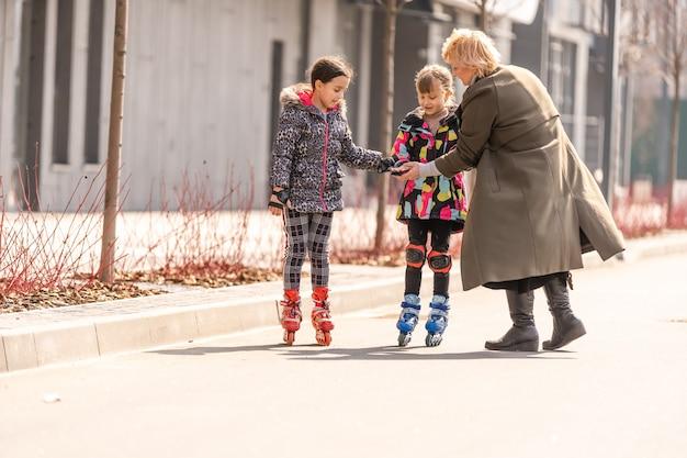 Grand-mère apprend à ses petites-filles à faire du patin à roulettes.