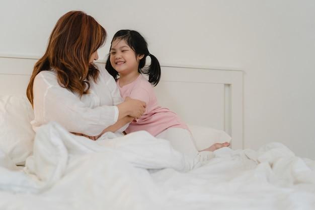 Grand-mère asiatique se détendre à la maison. senior chinois, grand-mère heureuse se détendre avec la jeune fille de petite-fille profiter de fermer ses yeux la surprise de jouer ensemble allongé sur le lit dans la chambre à la maison à la nuit concept.