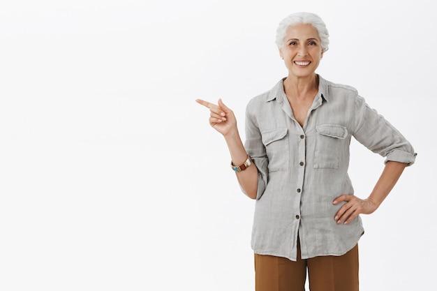 Grand-mère assez souriante pointant le doigt à gauche et montrant la publicité