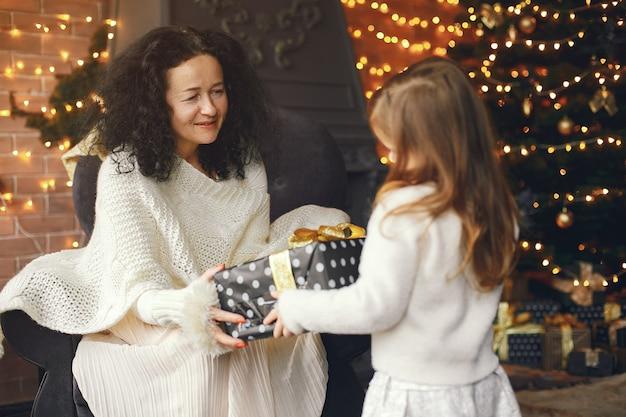 Grand-mère assise avec sa petite-fille. célébrer noël dans une maison chaleureuse. femme dans un pull en tricot blanc.