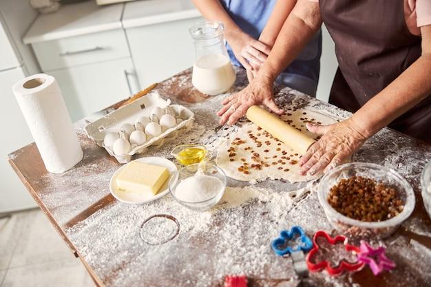 Grand-mère attentionnée enseignant à sa petite-fille une recette de biscuits