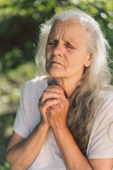 La grand-mère aux cheveux gris prie à l'extérieur.
