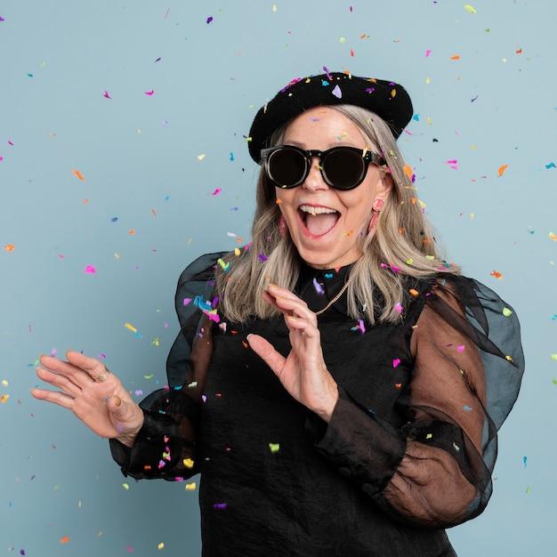 Grand-mère cool célébrant avec des confettis