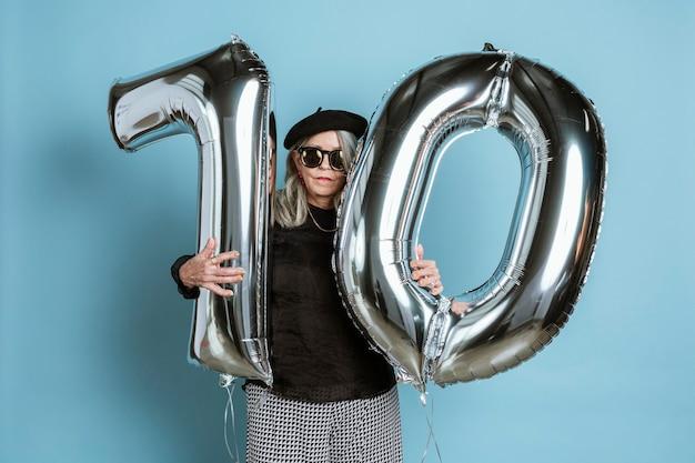 Grand-mère cool célébrant son 70e anniversaire avec des ballons