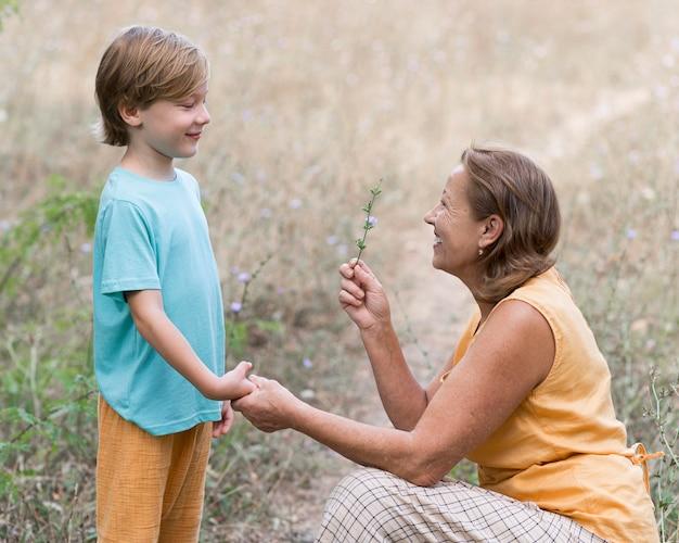 Grand-mère coup moyen tenant une fleur