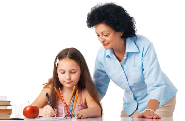 Grand-mère debout au-dessus de sa petite-fille et l'aidant à faire ses devoirs