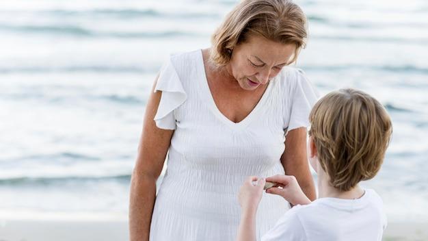 Grand-mère et enfant à coup moyen à la plage