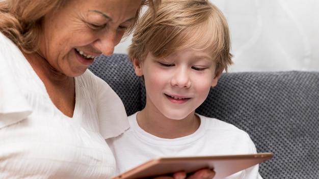 Grand-mère et enfant avec gros plan de tablette