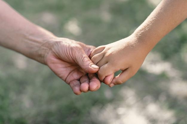 Grand-mère et enfant se tiennent la main
