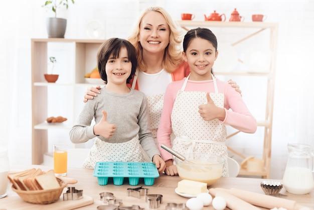 Grand-mère avec des enfants regardant la caméra dans la cuisine