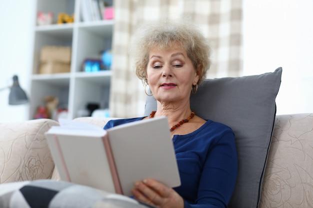 Grand-mère est assise à la maison et lit avec enthousiasme