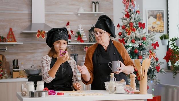 Grand-mère expliquant à petit-enfant comment faire un dessert traditionnel de pain d'épice fait maison de noël