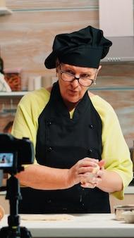 Grand-mère faisant un vlog de cuisine, s'enregistrant devant la caméra. chef influenceur blogueur à la retraite utilisant la technologie internet pour communiquer, bloguer sur les réseaux sociaux avec un équipement numérique