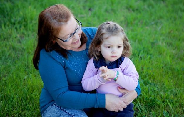 Grand-mère fière avec sa petite-fille assise sur l'herbe