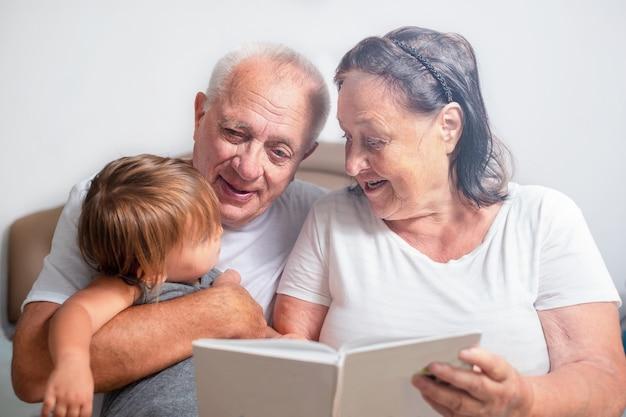 Grand-mère et grand-père lisent un livre à un enfant. les seniors passent du temps avec leur arrière-petite-fille
