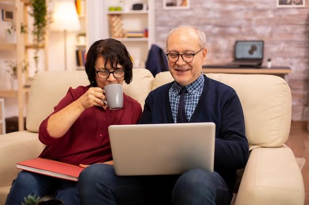 Grand-mère et grand-père utilisant un ordinateur portable pour discuter avec leurs petits-fils. personnes âgées utilisant la technologie moderne