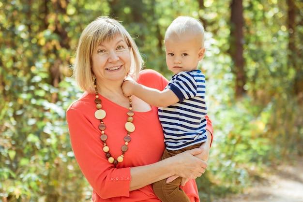 Grand-mère heureuse avec petit-fils embrassant en plein air