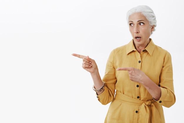 Grand-mère impressionnée et surprise regardant et pointant vers la gauche, haletante étonnée