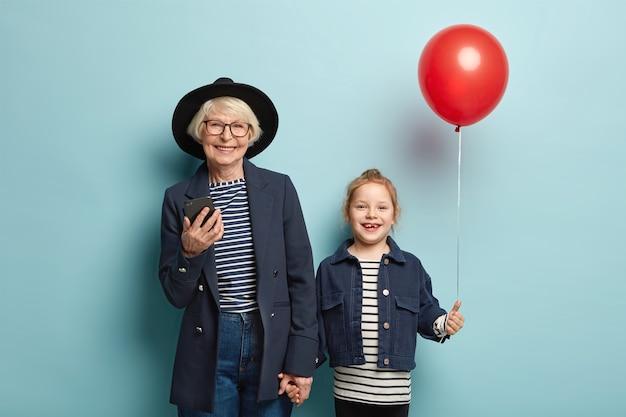 Une grand-mère joyeuse aux cheveux gris utilise un gadget moderne et surfe sur internet