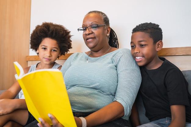 Grand-mère lisant un livre aux petits-enfants.