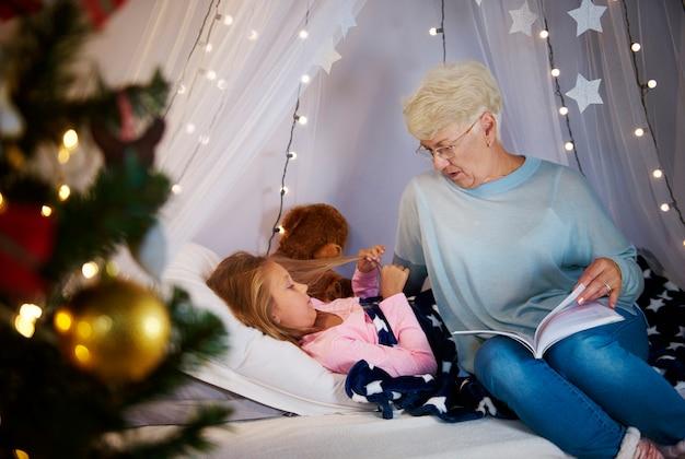 Grand-mère lisant un livre d'histoires à sa petite-fille