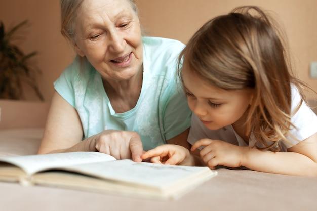 Grand-mère lit un livre éducatif à sa petite-fille