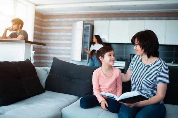 Grand-mère lit un livre à sa petite-fille. père travaille sur un ordinateur. maman cuisine dans la cuisine. grande famille à la maison.
