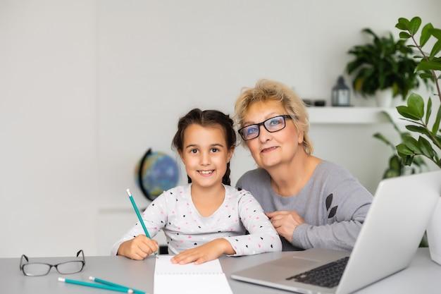 Grand-mère mature aidant l'enfant à faire ses devoirs à la maison. une vieille grand-mère satisfaite aidant sa petite-fille à étudier dans le salon. petite fille écrivant sur un ordinateur portable avec un professeur principal assis à côté d'elle