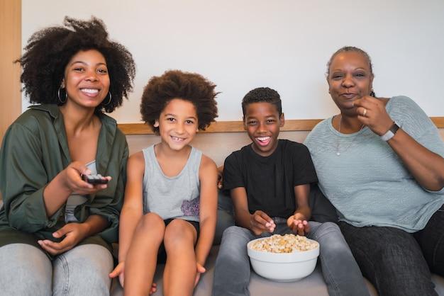 Grand-mère, mère et enfants regardant un film à la maison.