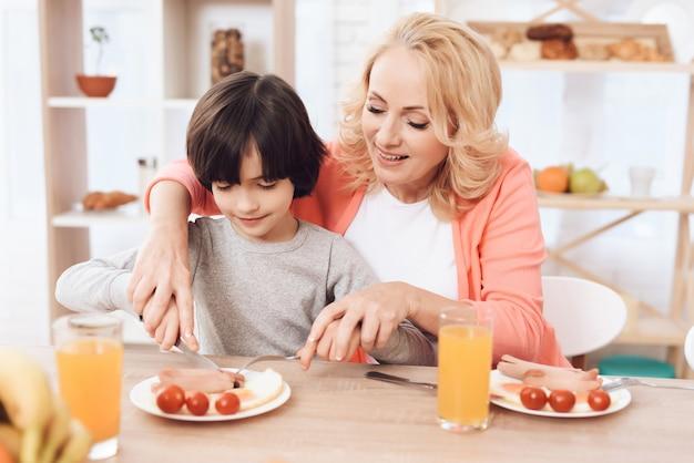 Grand-mère nourrit le petit-déjeuner