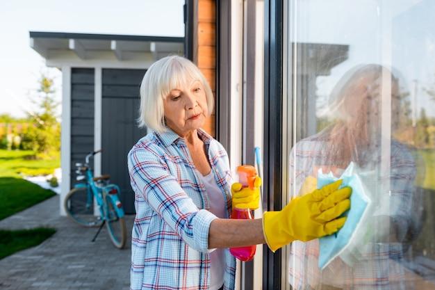 Grand-mère occupée. belle grand-mère aux cheveux blonds se sentant occupée tout en lavant les fenêtres à l'extérieur de la maison