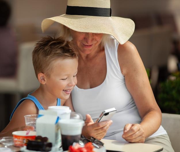 Grand-mère et petit-fils s'amusant avec smartphone sur une terrasse de café