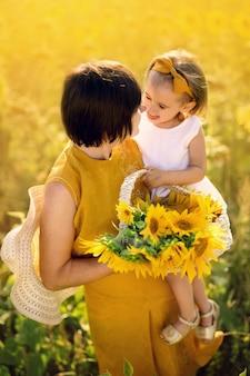 Grand-mère Et Petite-fille Dans Un Champ De Tournesols Tiennent Un Panier De Fleurs Et Une Communication émotionnelle Mignonne Photo Premium