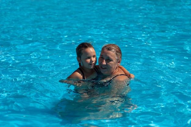 Grand-mère et petite-fille dans la piscine, une belle grand-mère et une douce petite-fille s'embrassent...