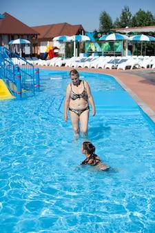 Grand-mère et petite-fille dans la piscine, une grand-mère blonde caucasienne regarde son grand-père de cinq ans...