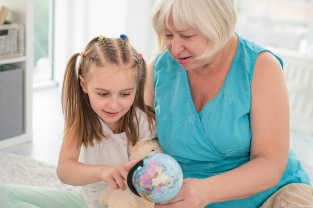 Grand-mère et petite-fille examinant le globe