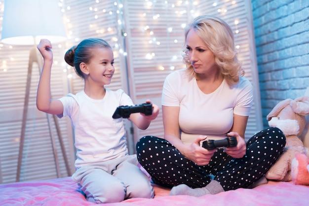 Grand-mère et petite-fille jouent à des jeux vidéo