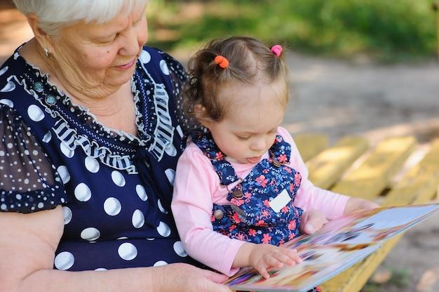 Grand-mère et petite-fille lisant le livre dans le parc