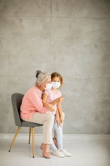 Grand-mère et petite-fille mignonne portant un masque respiratoire